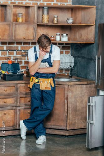 Fototapeta pensive young repairman looking at broken refrigerator in kitchen obraz na płótnie