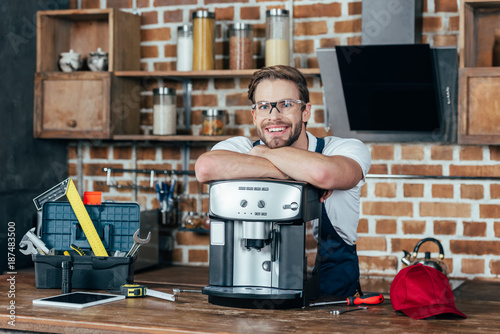 Fototapeta handsome young repairman leaning at coffee machine and smiling at camera obraz