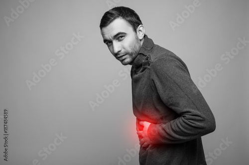 Fotografia, Obraz  young man holding his sick stomach in pain, isolated on gray background, monochr