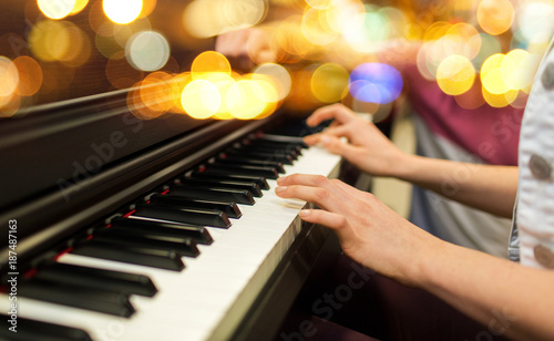 close up of woman hands playing piano over lights Fototapeta