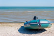 green rubber inflatable motor boat moored on the seashore, on a sunny summer day, against a blue sea and blue sky. Recreation, sport, fishing, tourism