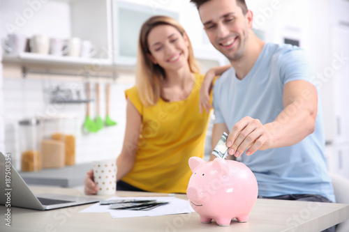 Fototapeta Young couple with piggy bank at home obraz