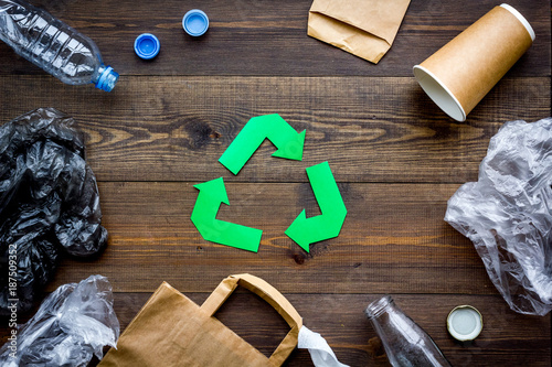 Fotografija  Green paper recycling sign among waste materials paper, plastic, polyethylene on