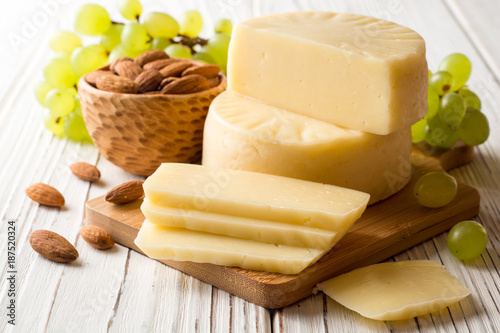 Staande foto Zuivelproducten Pieces of cheese on wooden board with almonds and green grape on white wooden background.