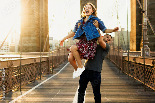 Plakát  Beautiful young man and woman pose on the Brooklyn Bridge in the rays of morning