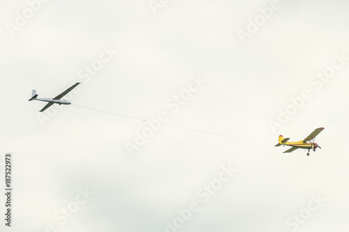 Yellow small light-engine sport plane flying in the sky pulls on a rope the glider plane