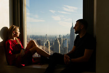Man And Woman Sit Together On The Windowsill With A Great Cityscape Of New York Behind Them
