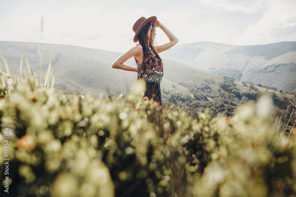 Fototapeta wanderlust and travel concept. stylish traveler woman in hat looking at mountains. hipster girl traveling on top of mountain, looking in front. space for text. atmospheric moment