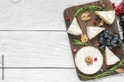 camembert cheese with grapes, pomegranate seeds, walnuts and rosemary on wooden cutting board