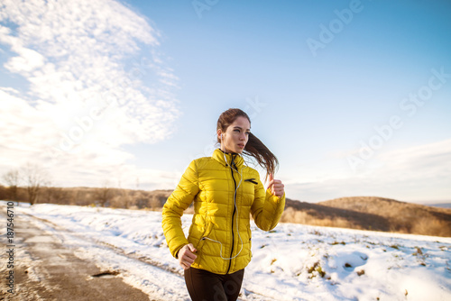 Poster Glisse hiver Portrait view of young satisfied serious motivated and focused sporty active girl with a fluffy ponytail in winter sportswear running in the snowy nature on the road.