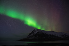 Northern Polar Lights Over The Mount And Ocean In Iceland