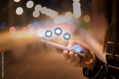 Woman hands using mobile smartphone in the street with icon social media and social network.