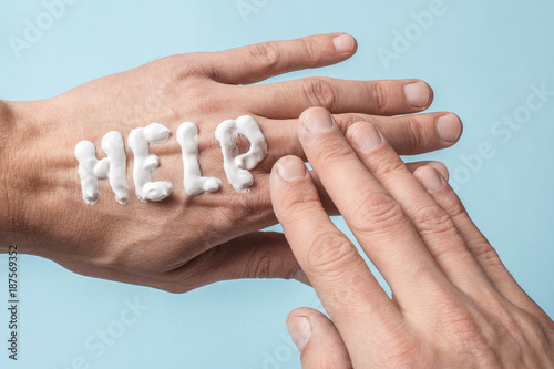 Fototapeta The word Help is written in cream. Painful dry hands of a man in cream or ointment. Blue background obraz