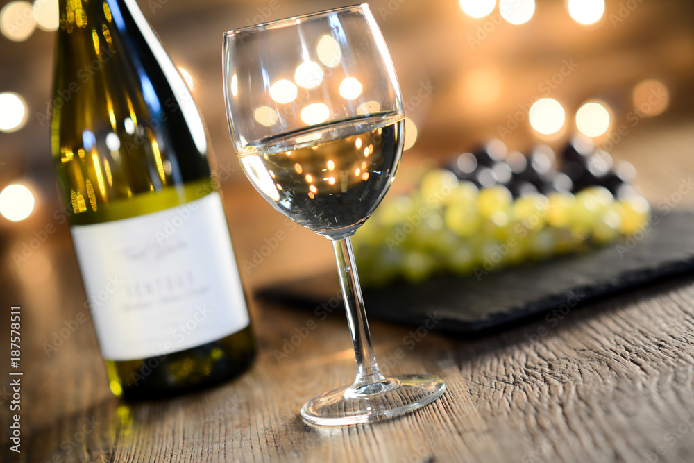 glass and bottle of white wine with copyspace empty wine label dim light in wooden restaurant table with a grape background