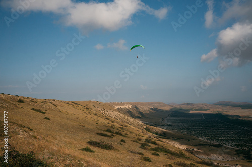 Parachutist gliding in blue sky over scenic landscape of Crimea, Ukraine, May 20 Canvas Print