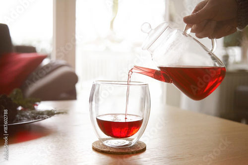 Woman pouring red tea into glass
