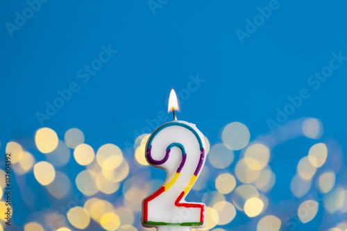 Fotografía  Number 2 birthday celebration candle against a bright lights and blue background