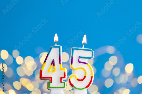 Photographie  Number 45 birthday celebration candle against a bright lights and blue backgroun