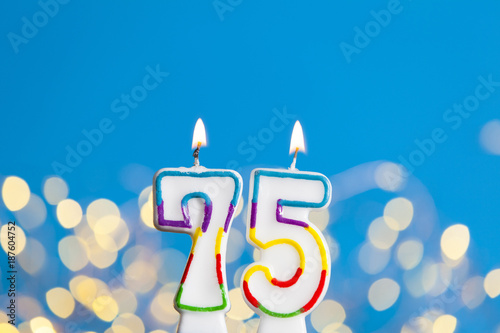 Number 75 Birthday Celebration Candle Against A Bright Lights And Blue Background