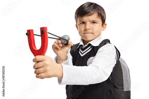 Fotografie, Tablou  Angry little schoolboy aiming with a slingshot and a rock
