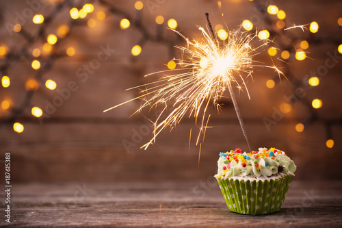 Fotomural  cupcake with sparkler on old wooden background