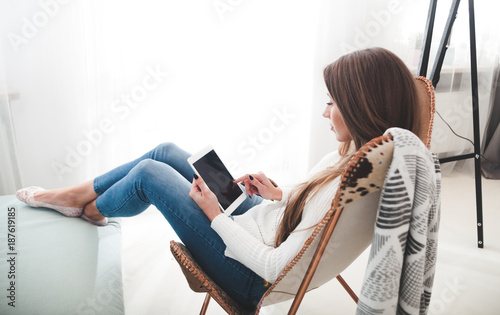 Woman at home sitting on modern chair and using tablet computer, relaxing in living room