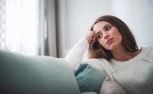 Sad Woman Sitting On Sofa At Home Deep In Thoughts, Thinking Concept