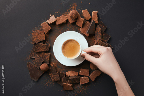 Fotografie, Obraz  cropped shot of female hand, cup of coffee, truffles and chocolate on grey surfa