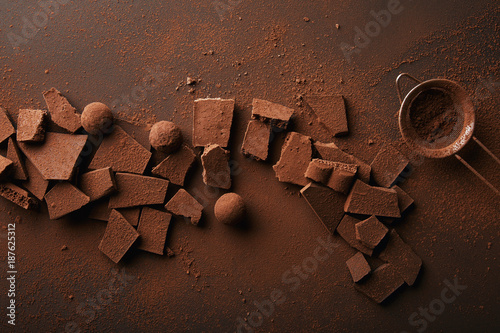 Fotografie, Obraz  top view of arrangement of various types of chocolate, truffles and sieve with c