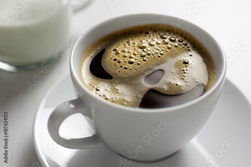 Fotografie, Obraz  Freshly poured black coffee with froth in white ceramic cup next to a milk jug on white