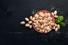 Pistachio Nuts On A Dark Woode...