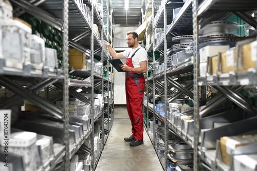Fotografía  Mitarbeiter im Lager mit KFZ-Ersatzteilen in einer Autowerkstatt // Employees in