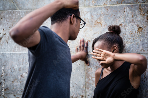 Fotografija Violent young man threatening his girlfriend with his fist outdoors