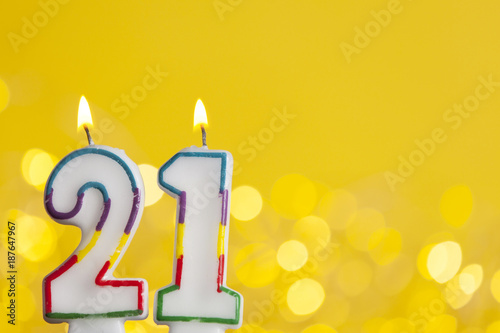 Number 21 Birthday Celebration Candle Against A Bright Lights And Yellow Background