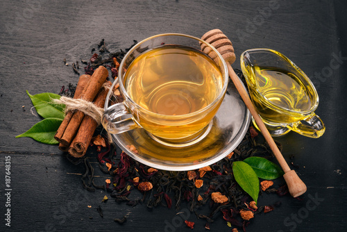 Staande foto Thee Tea in a cup of cinnamon and honey on a wooden background. Hot drink Top view. Copy space.