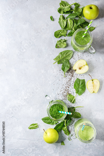 Fototapeta Variety of three color green spinach kale apple yogurt smoothie in mason jars with retro cocktail tubes and ingredients above over gray texture background. Healthy vegan detox eating. Top view, space obraz na płótnie