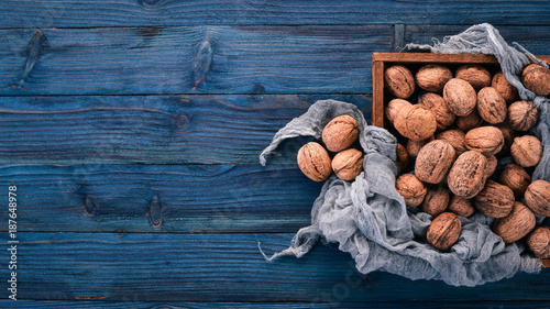 Fotografía  Walnut. In a box on a wooden background. Top view. Copy space.