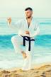 Joyful guy practising karate kata poses