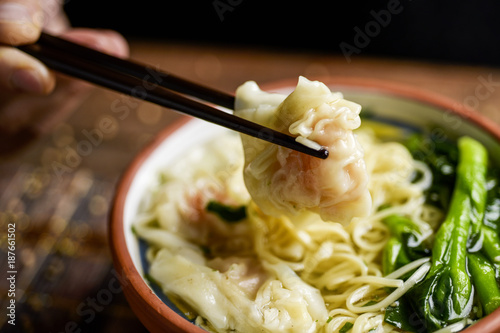 man eating shrimp wonton noodle soup with choy sum