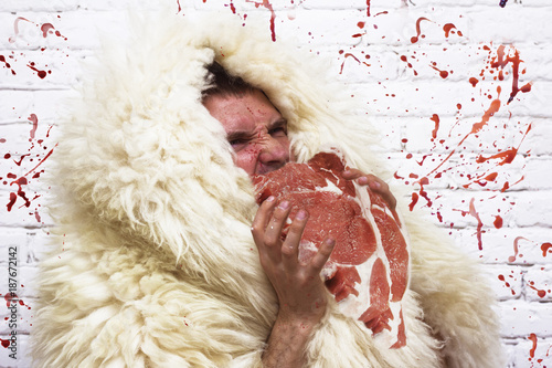 Photo  hungry wild man in a white skin with meat