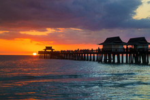 Florida City Of Naples Pier During Beautiful Sunset After Warm Sunny Day, Beach Architecture Of Pier Above The Sea With Awesome Colourful Setting Sun Background