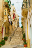 Fototapeta Na drzwi - Medieval old town typical narrow street with stairs in Valletta on the island of Malta. Colorful red, yellow, blue balconies and doors and green plants near traditional style stone buildings.