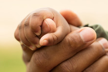 African American Father Holding His Daughters Hands.