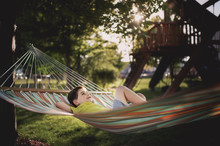 Boy With Hands Behind Head Lying In Hammock At Park