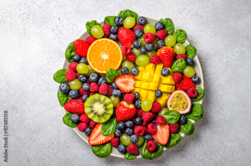 Foto op Aluminium Vruchten Fruit platter with various fresh strawberry, raspberry, blueberry, tangerine, grape, mango, spinach on a light stone background. Copy space, top view, horizontal