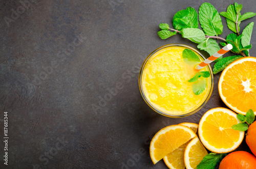 One glass of freshly pressed orange juice with a straw and mint leaves on a dark black stone background. Top view, horizontal image