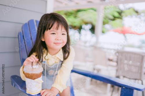 Foto op Plexiglas Bakkerij Asian little girl drinking lemon tea in outdoor cafe on summer.