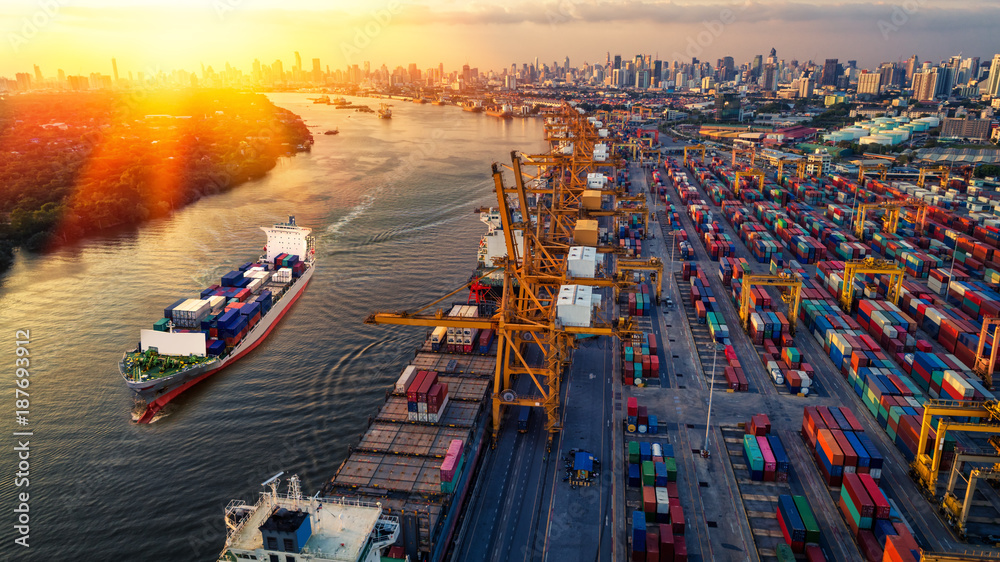 Fototapeta Container ship in import export and business logistic. Trade Port. Shipping, cargo to harbor and Cargo plane with working crane bridge in shipyard at sunrise, logistic import export and transport indu