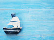 White and blue sailboat on blue wooden background