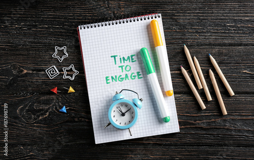 Fotografie, Obraz  Notebook with written phrase TIME TO ENGAGE, clock and markers on wooden backgro